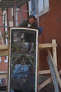 Tim Jones of Pearl River Glass Studio remove the stained glass window from Ventress Hall in Oxford, Miss. on Wednesday, December 1, 2010 so that it may be repaired..