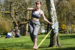 © Licensed to London News Pictures. 04/04/2020. London, UK. A woman walking on a balancing rope in Finsbury Park, north London on a warm and sunny day, during coronavirus lockdown. According to the Met Office, temperature in London is likely to reach 20 degrees this weekend. The Government has ordered that people go out only for food and health reasons or for work, and keep 2 meters away from other people at all times to slow the spread of the virus and reduce pressure on the NHS. <br /> <br /> ***Permission Granted***<br /> <br /> Photo credit: Dinendra Haria/LNP