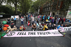 © Licensed to London News Pictures. 07/10/2019. London, UK.  Extinction Rebellion protestors block the road at Millbank near Parliament in central London . Activists are converging on Westminster blockading roads in the area for at least two weeks calling on government departments to 'Tell the Truth' about what they are doing to tackle the Emergency. Photo credit: Peter Macdiarmid/LNP