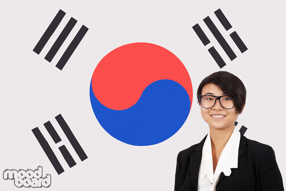 Portrait of young businesswoman smiling over Korean flag