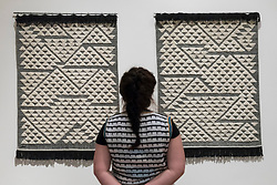 "© Licensed to London News Pictures. 09/10/2018. LONDON, UK. A visitor views ""Vicara Rug I"" and ""Vicara Rug II"", 1959, by Anni Albers in collaboration with Inge Brouard Brown.  Preview of the UK's first exhibition of works by German artist Anni Albers at Tate Modern who used the ancient art of hand-weaving to produce works of modern art.  Over 350 of her artworks from major collections from Europe and the US are on show 11 October to 27 January 2019.  Photo credit: Stephen Chung/LNP"