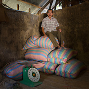 Pech Boeun sitting on top of the bags of rice in the rice store on his farm. Pech is the leader of Banan farming co-operative. Banan, Cambodia. Part of the VSO / Accenture IMA4P project in Cambodia.