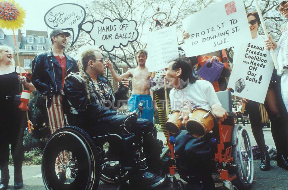 Sex Maniacs demonstration for sexual freedom, two disabled men in wheelchairs in front of group holding signs, London 1980's