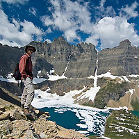hiker with backback above iceberg lake, overlooking iceberg lake, glacier national park, montana, usa, crown of the continent