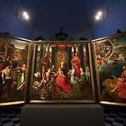 Altar piece of John the Evangelist and John the Baptist. Hans Memling (c. 1430 - 1494) was commissioned to paint this triptych by the monastic community of the St John's Hospital. On the outside of the wings are the portraits of the donors--two monks and two nuns who held important offices in the foundation and who paid for this work. Depicted in the center of the panel is a 'Sacra conversazione', a gathering of saints and angels around the Virgin and Child. Both St. Barbara, who sits just in front of her tower, and St. Catherine, identified by her wheel, are closely associated with the monastic life. Flanking the Virgin are the hospital's patron saints: John the Baptist with the Lamb and John the Evangelist with the chalice. Old St. John's Hospital is one of Europe's oldest surviving hospital buildings that dates to the 11th century. It originally treated sick pilgrims and travelers. A monastery and convent was later added. It is now a museum.