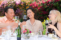 Three friends toasting at outdoor table