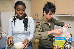 University students making breakfast in shared accommodation kitchen,