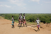 A group of young Karo tribe boys with AK-47 rifle . Omo Valley, Ethiopia