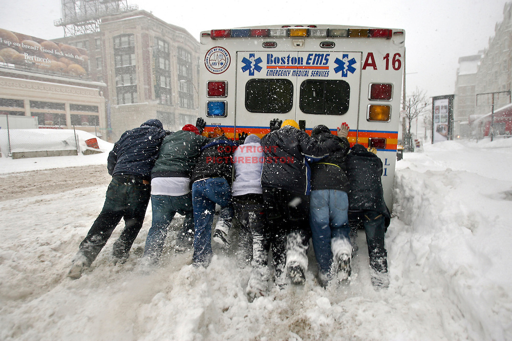 """Final Push""  A city of Boston ambulance is freed from the snow by people who were passing by as the quick Blizzard continued this morning."