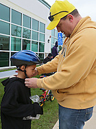 Terry Besta (from right) adjusts the helmet on his son, Alex Beste, 7, during the 2nd Annual Bike Rodeo at Kaplan University, 3165 Edgewood Parkway, in Cedar Rapids on Saturday morning, April 28, 2012. Kaplan University gave away 30 helmets at the event. (Stephen Mally/Freelance)