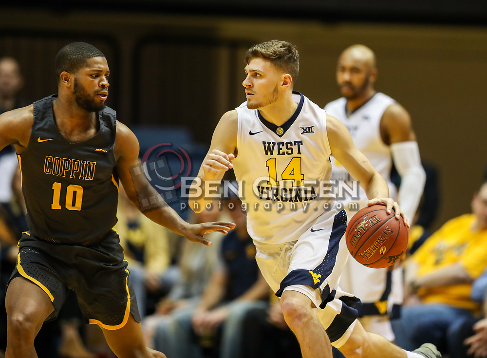 Dec 20, 2017; Morgantown, WV, USA; West Virginia Mountaineers guard Chase Harler (14) dribbles the ball and is guarded by Coppin State Eagles guard Karonn Davis (10) during the first quarter at WVU Coliseum. Mandatory Credit: Ben Queen-USA TODAY Sports