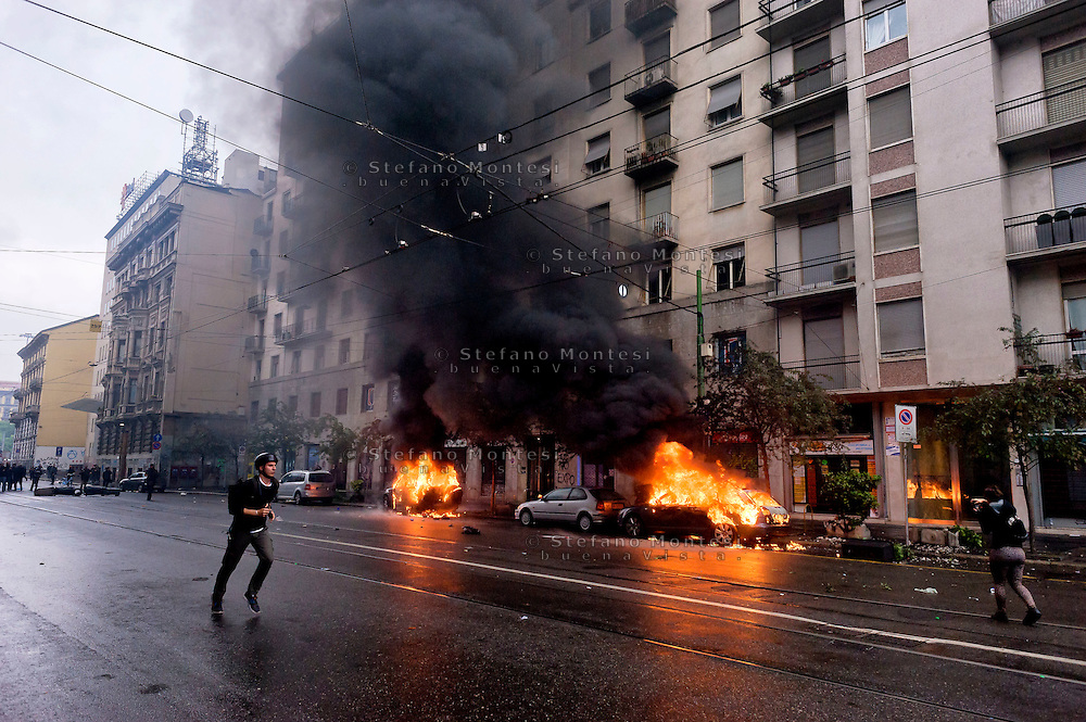 Milano 1 Maggio 2015<br /> Mayday  NoExpo  <br /> Scontri manifestanti polizia durante la manifestazione a Milano,contro l'apertura dell'Esposizione universale Milano 2015. Automobili incendiate dai manifestanti<br /> Milan, May 1, 2015<br /> Mayday NoExpo<br /> Clashes  protesters against police during the demonstration in  downtown Milan, to protest against Universal Exposition Milano 2015. Cars set on fire by protesters