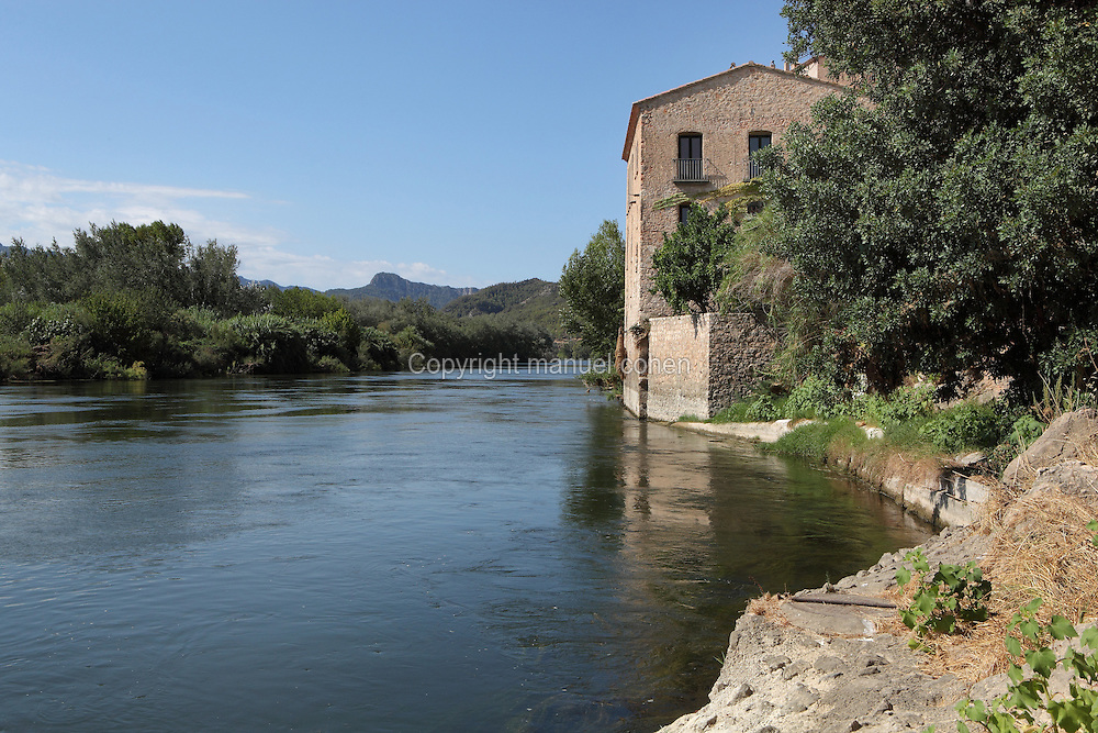 House along the banks of the Ebro river between Mora del Ebre and Miravet with mountains in the distance, Tarragona, Spain. In this region the river is near the end of its course, passing through gorges and mountainous scenery before flowing out through the Ebro Delta into the Mediterranean Sea. Picture by Manuel Cohen