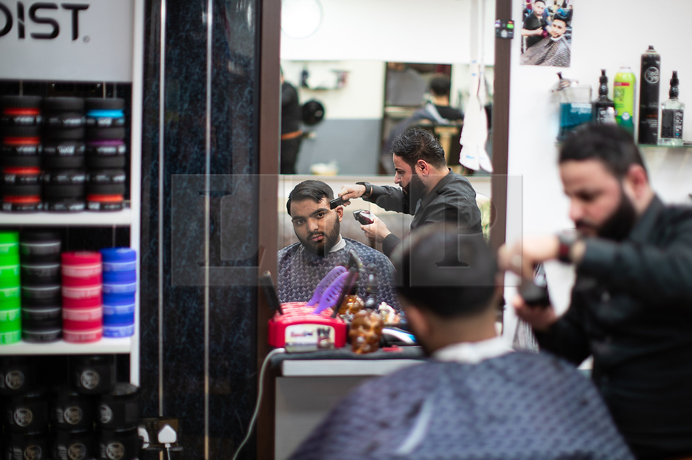 © Licensed to London News Pictures. 05/06/2019. Manchester, UK. MOHAMMAD BUTT (22 from Cheetham Hill) gets a hair cut from barber MAJID MOHAMMAD KARIM (34) of Top Barbers . People celebrate Eid-ul-Fitr , the end of a month of fasting during Ramadan , in Rusholme in Manchester . Photo credit: Joel Goodman/LNP
