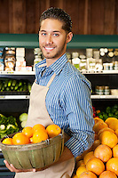 Happy salesperson with basket full of oranges in market