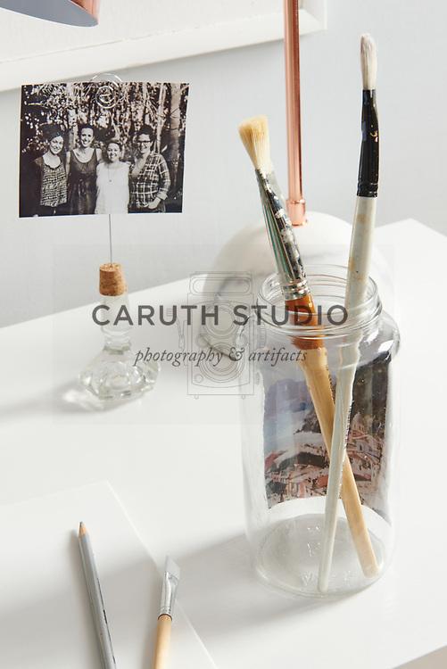 Photo inside glass jar holding paintbrushes