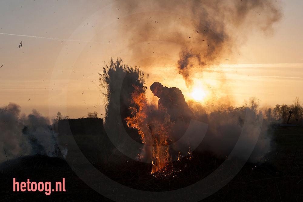 Nederland, Belt-Schutsloot 27 dec 2016 Rietsnijders gebroeders Klaver uit het Overijsselse Belt-Schutsloot (kop van Overijssel) maken gebruik van het mooie weer om aan het eind van het jaar nog een perceel riet te snijden. Het riet wordt gebruikt voor het dekken van daken. In de kop van overijssel wordt nog veel riet geteeld. Overtollig afval wordt aan het einde van de dag in brand gestoken. foto: Cees Elzenga Hollandse-Hoogte