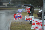 Kathy King holds a campaign sign as voters go to the polls in the rain at the National Guard Armory in Oxford, Miss. on Tuesday, November 2, 2010.
