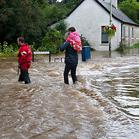 Comrie Flooding....27.08.12<br /> Firefighters make their way through floodwaters on Barrack Road in Comrie after the River Ruchil burst its banks and turned Barrack Road, Camp Road and Dalginross Road into Rivers<br /> Picture by Graeme Hart.<br /> Copyright Perthshire Picture Agency<br /> Tel: 01738 623350  Mobile: 07990 594431