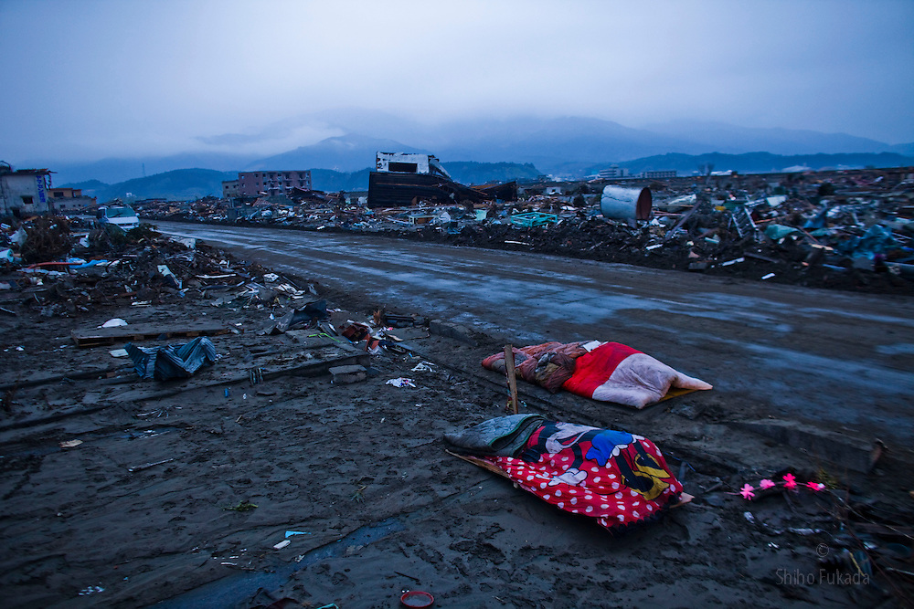 Two dead bodies are left covered by blanket in rubbles of Rikuzentakata, Iwate prefecture, Japan, March 15, 2011.  In this town of 23,000, more than one in 10 people is either dead or has been missing since the earthquake.
