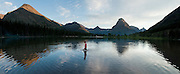 "A boy walks in Pray Lake beneath Sinopah Mountain (8271 feet or 2521 meters) at sunset in Glacier National Park, Montana, USA. Since 1932, Canada and USA have shared Waterton-Glacier International Peace Park, which UNESCO declared a World Heritage Site (1995) containing two Biosphere Reserves (1976). Rocks in the park are primarily sedimentary layers deposited in shallow seas over 1.6 billion to 800 million years ago. During the tectonic formation of the Rocky Mountains 170 million years ago, the Lewis Overthrust displaced these old rocks over newer Cretaceous age rocks. Glaciers carved spectacular U-shaped valleys and pyramidal peaks as recently as the Last Glacial Maximum (the last ""Ice Age"" 25,000 to 13,000 years ago). Of the 150 glaciers existing in the mid 1800s, only 25 active glaciers remain in the park as of 2010, and all may disappear by 2020, say climate scientists. (Panorama stitched from 4 overlapping images.)"