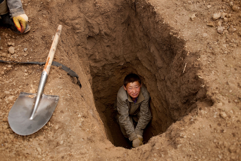 "A young man in a pit mine just large enough for himself. He is looking for the ""gold dirt"". The sought after dirt is of a different shade that indicates it may contain gold. The dirt is then loaded into sacks or into flatbed trucks and brought to an area with water so it can be panned in order to separate the gold flecks from the dirt."
