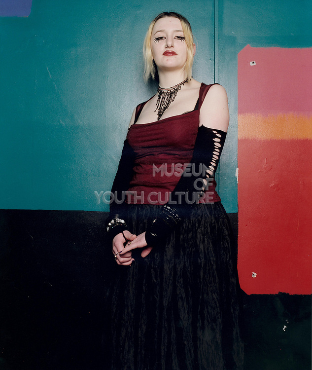 Young goth woman standing slightly to the side posing with serious expression.
