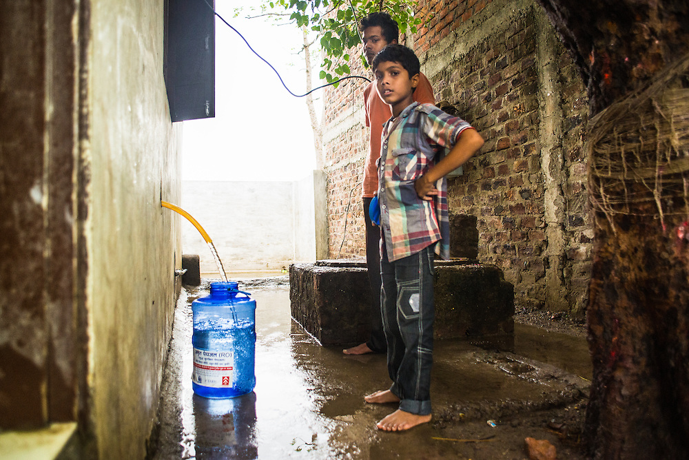 CAPTION: Child collecting water directly from the RO plant. LOCATION: Rahul Gandhi Nagar, Indore, Madhya Pradesh, India. INDIVIDUAL(S) PHOTOGRAPHED: Unknown.