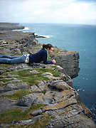 A student looks out over an oceanside cliff during a study abroad trip to Europe.