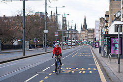Edinburgh, Scotland, UK. 29 March, 2020. Life in Edinburgh on the first Sunday of the Coronavirus lockdown. Streets deserted, shops and restaurants closed, very little traffic on streets and reduced public transport. Pictured; Princes Street mostly empty although cyclists are enjoying the quiet streets. Iain Masterton/Alamy Live News