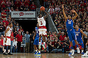 Louisville guard Chris Jones, center, has his shot contested by Kentucky forward Karl-Anthony Towns in the first half. <br /> <br /> The University of Louisville hosted the University of Kentucky, Saturday, Dec. 27, 2014 at The Yum Center in Louisville.