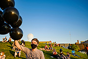 21 JULY 2020 - DES MOINES, IOWA: A volunteer hands out black balloons before a memorial and vigil for Representative John Lewis. About 300 people attended a vigil for the late Representative John Lewis (D-GA) in Poppajohn Sculpture Park in Des Moines Tuesday night. Rep. Lewis died from pancreatic cancer on July 17, 2020.              PHOTO BY JACK KURTZ