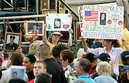 Family members of victims of the World Trade Center attack holds pictures of their loved ones at the site of the disaster on the fourth anniversary of the attack in New York September 11, 2005.