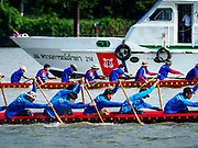 29 OCTOBER 2018 - PHRA PRADAENG, SAMUT PRAKAN, THAILAND: Racing long boats being rowed downriver pass a Thai Coast Guard boat during the long boat races in Phra Pradaeng. The longboat races go about one kilometer down the Chao Phraya River to the main pier in Phra Pradaeng. The boats are crewed by about 20 oarsmen. Longboat racing traditionally marks the end of the Buddhist Rains Retreat (called Buddhist Lent) in Thai riverside communities.       PHOTO BY JACK KURTZ