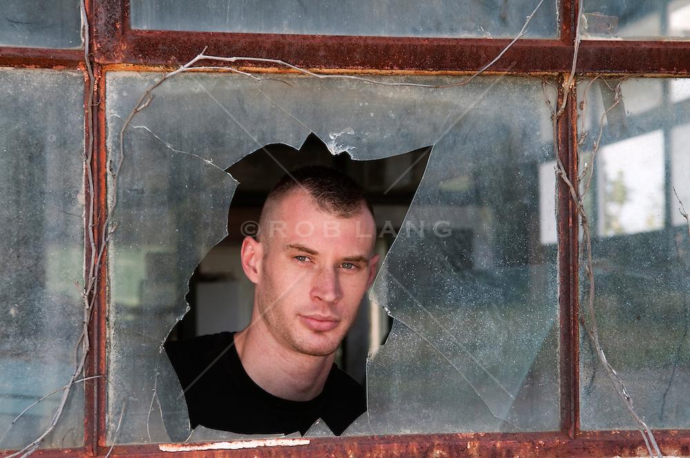 portrait of a man looking out a broken window