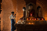 Myanmar lighting candles in a Buddhist temple