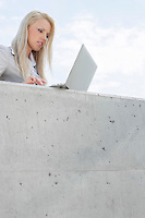 Young female business executive using laptop on terrace against sky