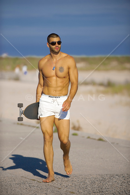shirtless man carrying a skateboard at Jones Beach State Park
