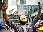 "02 JUNE 2013 - BANGKOK, THAILAND:   A man wearing a Guy Fawkes mask leads anti-government protesters through Bangkok skywalk system. The so called White Mask protesters are strong supporters of the Thai monarchy. About 300 people wearing the Guy Fawkes mask popularized by the movie ""V for Vendetta"" and Anonymous, the hackers' group, marched through central Bangkok Sunday demanding the resignation of Prime Minister Yingluck Shinawatra. They claim that Yingluck is acting as a puppet for her brother, former Prime Minister Thaksin Shinawatra, who was deposed by a military coup in 2006 and now lives in exile in Dubai.   PHOTO BY JACK KURTZ"