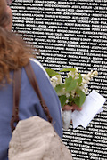 """Flowers in hand a woman searches for a name on the Traveling Vietnam Veterans Memorial, the """"Traveling Wall"""",  during its visit to Petoskey, Michigan."""