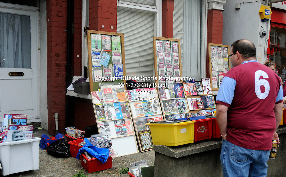21/08/2010 - Premiership Football - West Ham United vs Bolton Wanderers - A West Ham fan views the selection of old programes outside someones house. - Photo: Charlie Crowhurst / Offside.