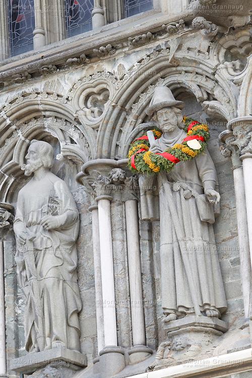 Statuen av St Jakob, som står på Vestfronten av Nidarosdomen..St. Jakob er pilegrimenes helgen. Hans minne er knyttet til Santiago de Compostela i Spania. Han er kledd som en pilegrim med stav, veske, kappe og hatt. St. Jakobs dag er 25. juli. Denne dagen henges en grønn krans med gule og røde innslag på St. Jakob statuen..Olavsfestdagene i Trondheim er norges største kirke- og kulturfestival. Olavsfestdagene arrangeres i juli hvert år...The St Olavs Festival is Norways largest church and culture festival. The festival is held every July in Trondheim, Norway.