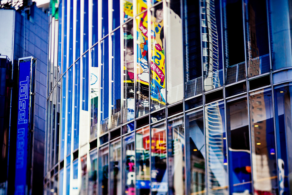 Buildings and advertisements reflected in the glass facades of other buildings in downtown Tokyo, Japan.