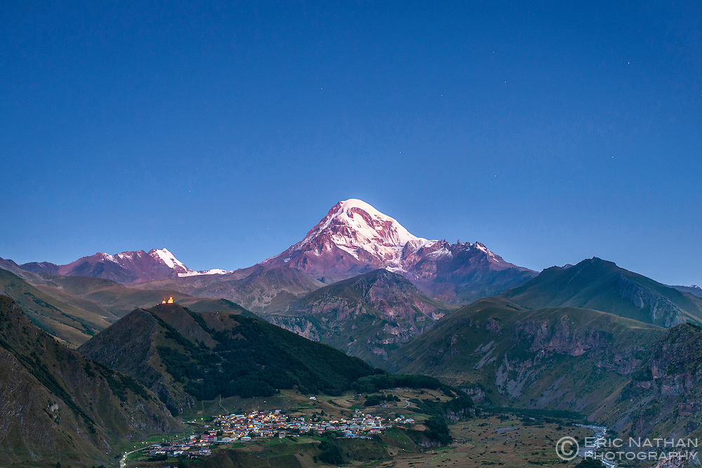 Dawn view of Mount Kazbek (5047m), the village of Gergeti and Gergeti Trinity Church in the Caucasus Mountains of northern Georgia.