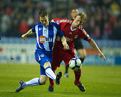 WIGAN, ENGLAND - Monday, March 8, 2010: Liverpool's Dirk Kuyt and Wigan Athletic's Gary Caldwell during the Premiership match at the DW Stadium. (Photo by David Rawcliffe/Propaganda)