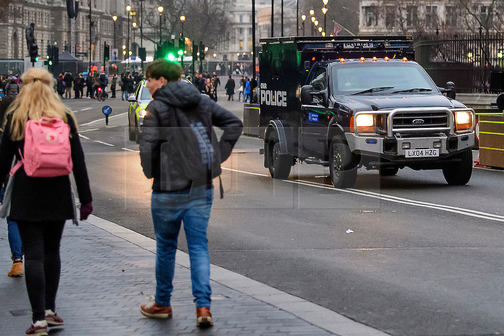 © Licensed to London News Pictures. 31/12/2016. London, UK. An armoured anti-terrorism vehicle, which belongs to the Counter Terrorist Specialist Firearms Officer unit (CTSFO) driving past the Houses of Parliament in Westminster, London ahead of tonight's New Year celebrations. Security surrounding this year's event has been heightened following a terrorist attack at a Christmas market in Berlin earlier this month. Photo credit: Ben Cawthra/LNP