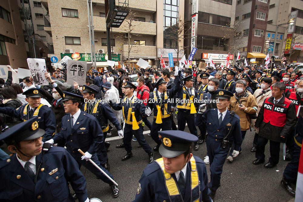 "February 5, 2017, Tokyo, Japan: A group of peace activists, heavily shielded by Tokyo Metropolitan Police officers, march through a demonstration of ultra-right wingers angered by APA Hotel's planned removal of a controversial history revisionist book from hotel rooms hosting athletes of the 2017 Sapporo Asian Winter Games. This took place in front of the hotel chain's Shinjuku Gyoen-mae branch. The book in question written by Toshio Motoya, the hotel chain's Chief Executive, claims the 1937 Nanjing Massacre was a fabrication. Writing under the pen name Seiji Fuji, Motoya's book entitled ""Theoretical Modern History II"" is placed in every APA Hotel room in Japan and sold at their reception desks. The Tokyo based APA Hotel group is one of the largest hotel chains in Japan with over 400 hotels across the country. In the past 2-3 years APA has benefitted from a tourism boom to Japan in which 40% of their guests are foreign visitors and half that amount are Chinese and Korean nationals. As a result, China and Korea have been outraged by APA and a large boycott began in late January by both countries. This led to APA announcing they would pull Motoya's books from athlete's rooms only during the Asian Winter Games, infuriating Japanese right wingers. The demonstrators at this event are part of a group who call themselves ""Group of Warriors Protecting the Nation"" (Gokoku Shishi no Kai). Photo by Torin Boyd."