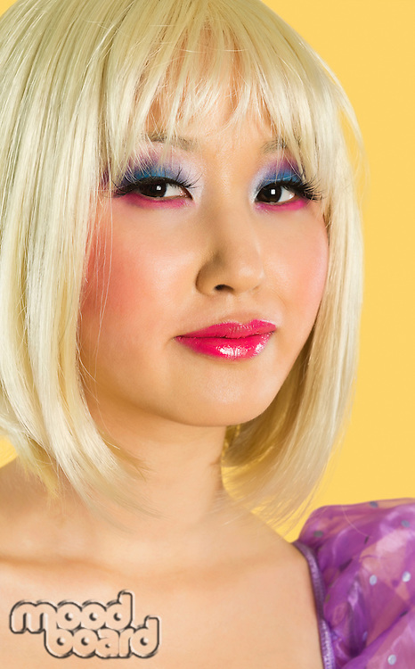 Portrait of young woman with blond hair and eyeshadow smiling against yellow background