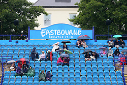 Spectators take shelter under umbrellas as rain halts play during day five of the AEGON International at Devonshire Park, Eastbourne.