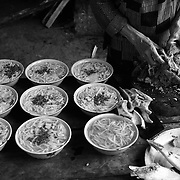 A woman prepares bowls of noodle soup at a weekend market in Tam Son, Ha Giang, Vietnam's northernmost province.